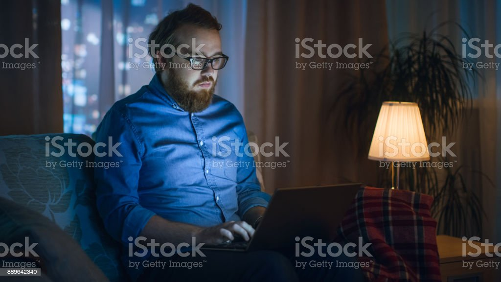 In the Evening Man Works on His Laptop While Sitting on Sofa in His...
