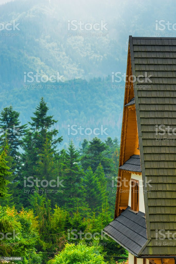 in the foreground in focus is the roof of the house, a view of the mountains and the forest stock photo