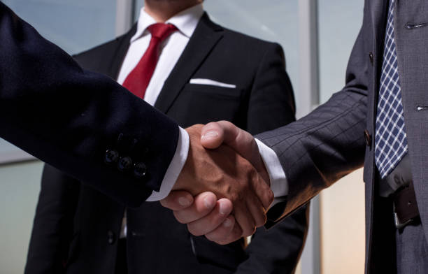in the foreground.business handshake business partners stock photo