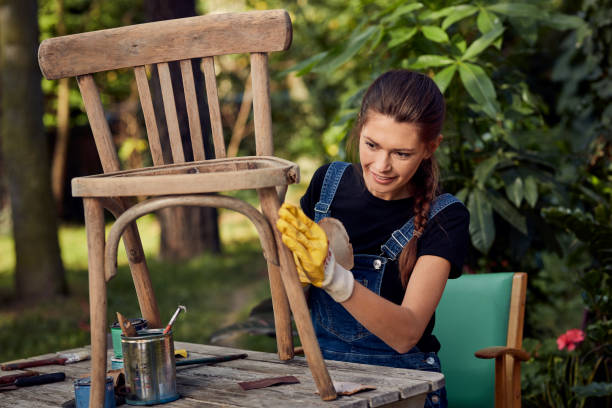 DIY in the garden. Grinding wooden chair Young woman working on diy project diy stock pictures, royalty-free photos & images