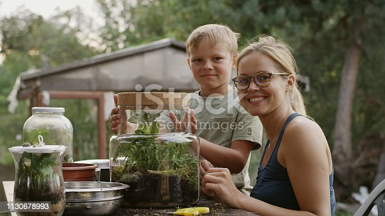 Young woman and her son working on diy project. Making forest in a jar