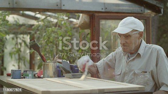 Home DIY. Man brushing wooden doors in garden