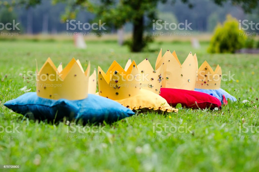 In the green meadow on the colored pads shunted stylized princess crowns. stock photo