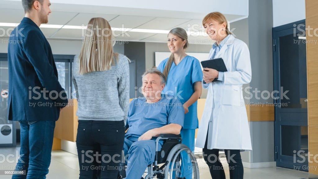En el vestíbulo del Hospital. Joven pareja visiten padres ancianos en silla de ruedas, es ayudado por la amable enfermera y médico. Feliz reunión familiar. Centro médico moderno nuevo con el mejor personal posible. - foto de stock