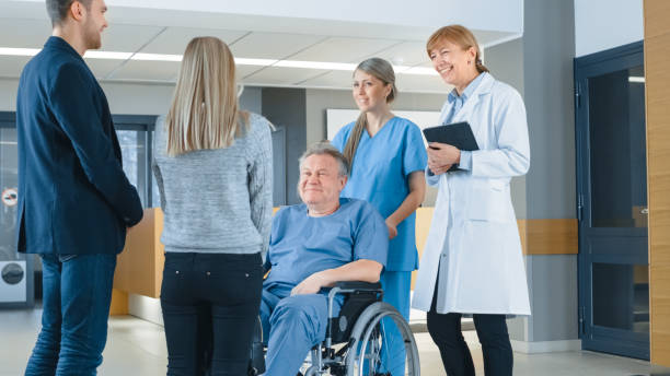 in the hospital lobby. young couple visiting elderly parent in a wheelchair, he's aided by friendly nurse and doctor. happy family reunion. new modern medical facility with best possible personnel. - family meeting stock photos and pictures