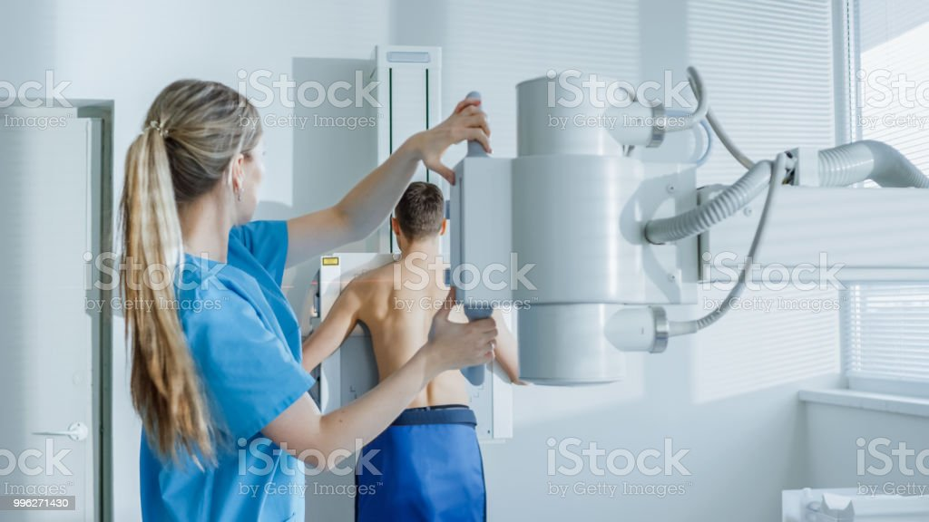 In the Hospital, Man Standing Face Against the Wall While Medical Technician Adjusts X-Ray Machine For Scanning. Scanning for Fractures, Broken Limbs, Chest, Cancer or Tumor. Modern Hospital with Technologically Advanced Medical Equipment. stock photo