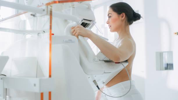 im krankenhaus, porträtaufnahme topless weibliche patienten unterziehen mammographie screening-verfahren. gesunde junge frau hat krebs vorbeugende mammographie scan. moderne krankenhaus mit hightech-maschinen. - mammografie stock-fotos und bilder