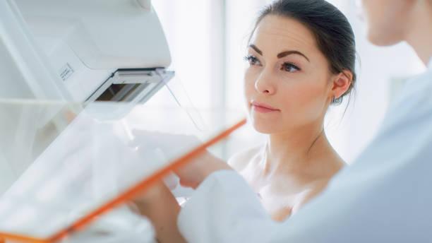 im krankenhaus, porträtaufnahme topless weibliche patienten unterziehen mammographie screening-verfahren. gesunde junge frau hat krebs vorbeugende mammographie scan. - mammografie stock-fotos und bilder