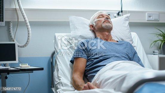 1049772134istockphoto In the Hospital, Senior Patient Lying in Bed, Sleeping. Modern Hospital Geriatrics Ward. 1043174772
