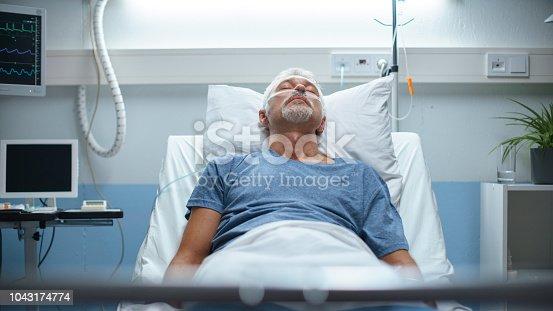 1049772134istockphoto In the Hospital, Senior Patient Lying in Bed, Sleeping. Modern Hospital Geriatrics Ward. 1043174774