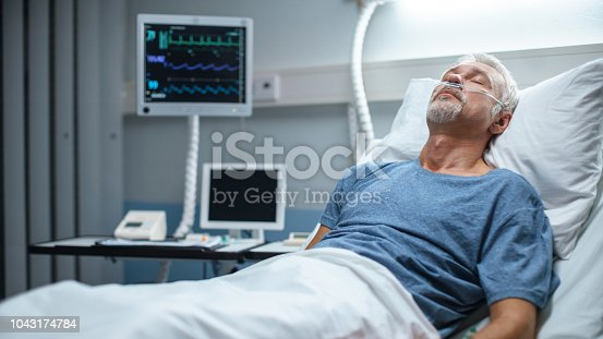1049772134istockphoto In the Hospital Senior Patient Rests, Lying on the Bed. Recovering Man Sleeping in the Modern Hospital Ward. 1043174784