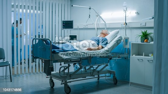 1049772134istockphoto In the Hospital Senior Patient Rests, Lying on the Bed. Recovering Man Sleeping in the Modern Hospital Ward. 1043174856