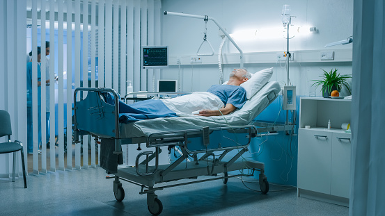 1049772134 istock photo In the Hospital Senior Patient Rests, Lying on the Bed. Recovering Man Sleeping in the Modern Hospital Ward. 1043174856