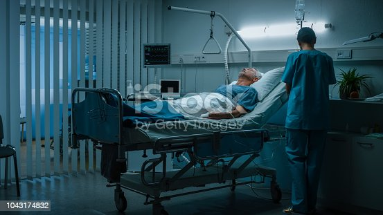 istock In the Hospital Senior Patient Rests on the Bed, Nurse in Ward Does Checkup. Recovering Man Sleeping in the Modern Hospital Ward. 1043174832