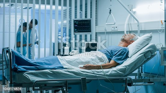 1049772134istockphoto In the Hospital Sick Man Rests, Lying on the Bed. Recovering Man Sleeping in the Modern Hospital Ward. 1043174824