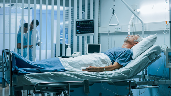 1049772134 istock photo In the Hospital Sick Man Rests, Lying on the Bed. Recovering Man Sleeping in the Modern Hospital Ward. 1043174824