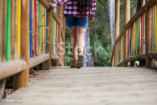 In the image there are feet with brown trekking boots. Feet appear walking on a bridge. You can also see part of the body of the girl wearing a plaid shirt and a backpack