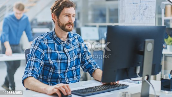 In the Industrial Engineering Facility: Portrait of the Handsome Smart Male Engineer Working on a Desktop Computer. In the Background Specialists and Technicians Working with Drafts and Drawings