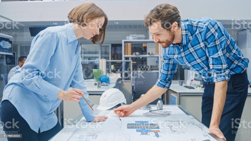 Young Female Designer Works with Chief Industrial Engineer, They have...