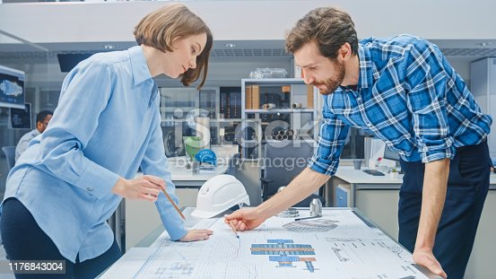 921019684istockphoto In the Industrial Engineering Facility: Young Female Designer Works with Chief Industrial Engineer, They have Discussion, Analyse and Correct Engine Design Technical Drafts that are Lying on the Table 1176843004