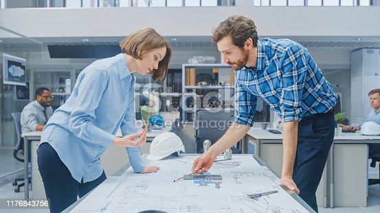 921019684 istock photo In the Industrial Engineering Facility: Young Female Designer Works with Chief Industrial Engineer, They have Discussion, Analyse and Correct Engine Design Technical Drafts that are Lying on the Table 1176843756