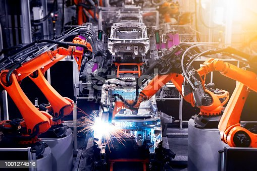 989526318 istock photo In the industrial production workshop, the robot arm of the automobile production line is working 1001274516