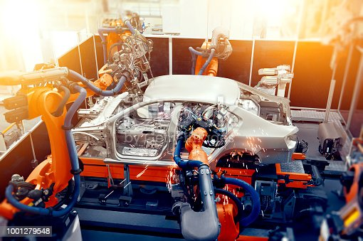 989526318 istock photo In the industrial production workshop, the robot arm of the automobile production line is working 1001279548