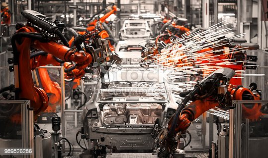 989526318 istock photo In the industrial production workshop, the robot arm of the automobile production line is working 989526286