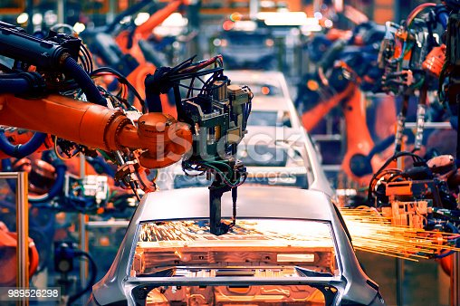 989526318 istock photo In the industrial production workshop, the robot arm of the automobile production line is working 989526298