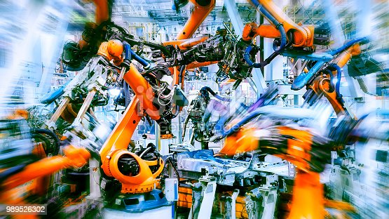 989526318 istock photo In the industrial production workshop, the robot arm of the automobile production line is working 989526302