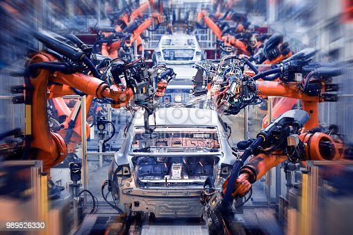 989526318 istock photo In the industrial production workshop, the robot arm of the automobile production line is working 989526330