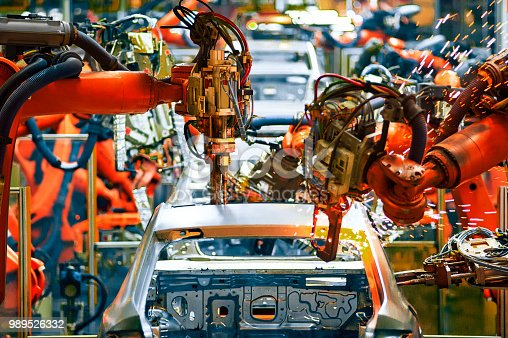 989526318 istock photo In the industrial production workshop, the robot arm of the automobile production line is working 989526332