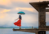 woman fashion dress standsing on the retro old cottage house in the lake, holding umbrella under raining season