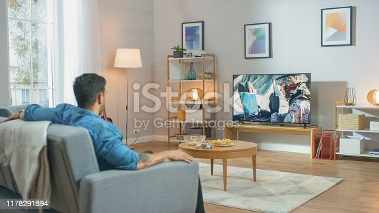 In the Living Room: Guy Relaxing on a Couch Watching War Movie on a TV. Modern Military Warfare Action with War Soldier Shown on a Television.
