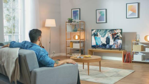 Im Wohnzimmer: Guy Relaxing on a Couch Watching War Movie on a TV. Modern Military Warfare Action mit Kriegssoldat auf einem Fernseher gezeigt. – Foto