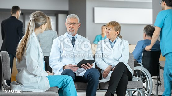 istock In the Lobby of the Hospital Three Professional Doctor Have Discussion while Sitting. They Use Tablet Computer. Busy Modern Hospital with Best Specialists and Medicare in Country. 1043634392