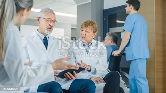 istock In the Lobby of the Hospital Three Professional Doctor Have Discussion while Sitting. They Use Tablet Computer. Busy Modern Hospital with Best Specialists and Medicare in Country. 995338632