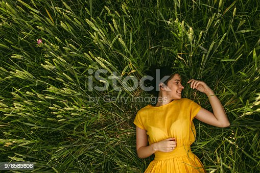 Young girl holding chamomile plant in her hands and enjoying the calm meadow