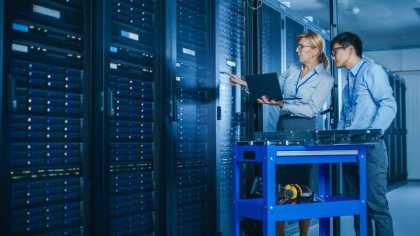 in het moderne data center: engineer en it specialist werken met server racks, op een pushcart apparatuur voor het installeren van nieuwe hardware. specialisten doen onderhoud en diagnostiek van de database. - datacenter stockfoto's en -beelden