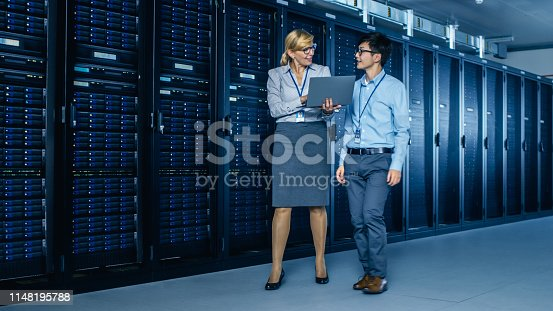 917307226istockphoto In the Modern Data Center: Engineer and IT Specialist Work with Server Racks, Talking, Doing System Maintenance Check with Laptop Computer. Specialists Doing Diagnostics of the Database. 1148195788
