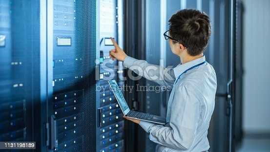 899720520istockphoto In the Modern Data Center: IT Engineer Standing Beside Open Server Rack Cabinets, Does Wireless Maintenance and Diagnostics Procedure with a Laptop. He Pushes Button. 1131198189