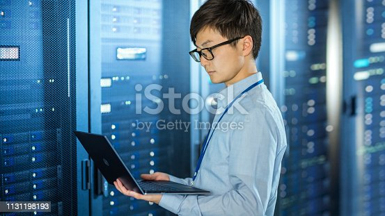 899720520istockphoto In the Modern Data Center: IT Engineer Standing Beside Server Rack Cabinets, Does Wireless Maintenance and Diagnostics Procedure with a Laptop. 1131198193