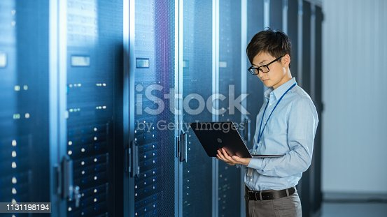 899720520 istock photo In the Modern Data Center: IT Engineer Standing Beside Server Rack Cabinets, Does Wireless Maintenance and Diagnostics Procedure with a Laptop. 1131198194