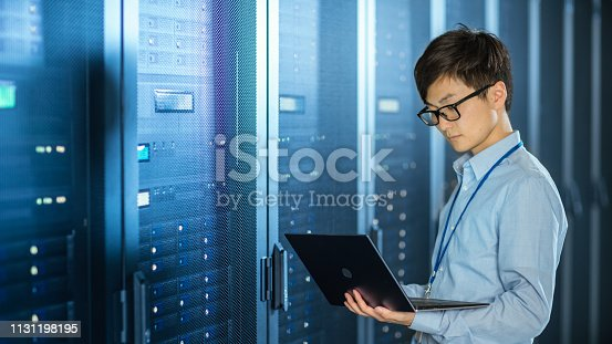 899720520 istock photo In the Modern Data Center: IT Engineer Standing Beside Server Rack Cabinets, Does Wireless Maintenance and Diagnostics Procedure with a Laptop. 1131198195