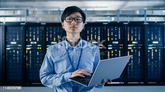 917307226istockphoto In the Modern Data Center: Portrait of IT Engineer Standing with Server Racks Behind Him, Holding Laptop and Looking at the Camera. Finishing Doing Maintenance and Diagnostics Procedure. 1148233796