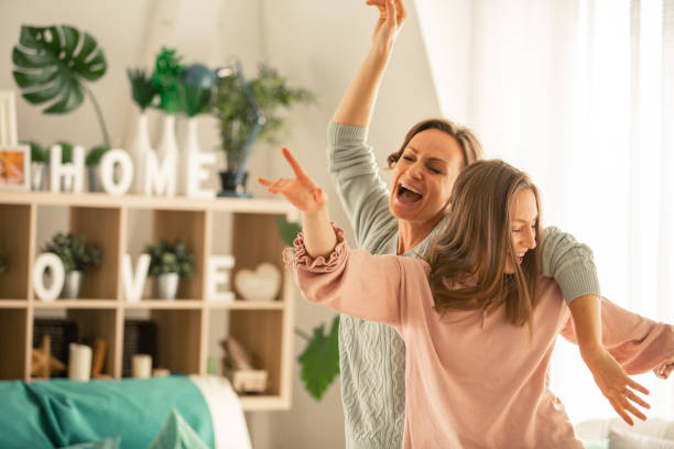 In the moment Mother and her daughter captured in the moment of pure joy and laughter while dancing and singing together in their living room. dancing stock pictures, royalty-free photos & images