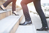 In the morning, businessman and businesswoman are walking up and down the stairs to work at the office.