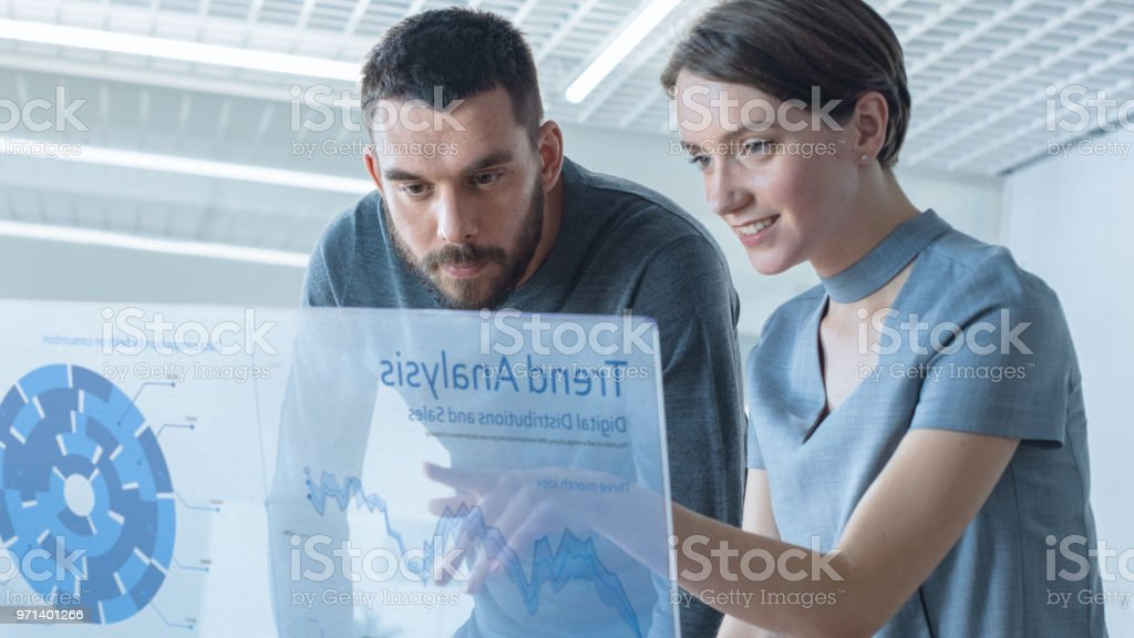 In the Near Future Male and Female Trade Agents Talk While Working on the Transparent Display Computer. Screen Shows Economical Graphs, Analysis of Trade, Futuristic User Interface. stock photo