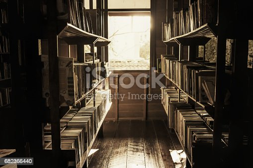 istock In the old library, the books on the shelves were cluttered, the light shining out of the window in a lonely atmosphere, vintage style. 682366440
