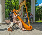 Russia, Pavlovsk Park, July 22, 2017 harpist playing in the Park for the flower festival